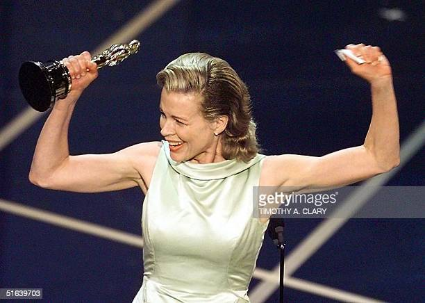 Actress Kim Basinger holds up her Oscar after winning the Best Supporting Actress Oscar for her role in 'LA Confidential' during the 70th Academy...