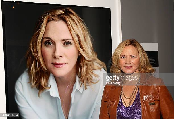 Actress Kim Cattrall poses for a photo next to her portrait at 'The Boomer ListPhotographs by Timothy GreenfieldSanders' exhibit at The Newseum on...