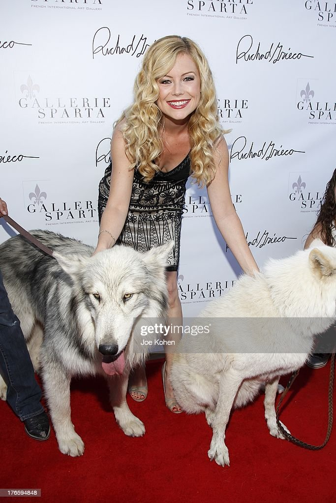 Actress Kim Poirier poses for a photo with Ranger and Maya, wolfs from the Wolfconnection.org at Richard Grieco's opening night gala for his one-man art exhibit 'Sanctum Of A Dreamer!' at Gallerie Sparta on August 15, 2013 in West Hollywood, California.