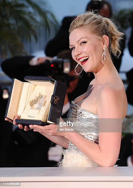 Actress Kirsten Dunst poses after winning Best Actress for the film 'Melancholia' at the Palme d'Or Winners Photocall at the Palais des Festivals...