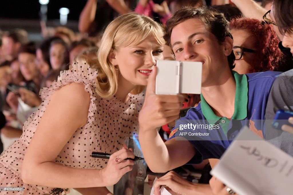 TOPSHOT - Actress Kirsten Dunst poses with fans and signs autographs the premiere of the movie 'Woodshock' presented in the 'Cinema nel Giardino' selection at the 74th Venice Film Festival on September 4, 2017 at Venice Lido. / AFP PHOTO / Tiziana FABI