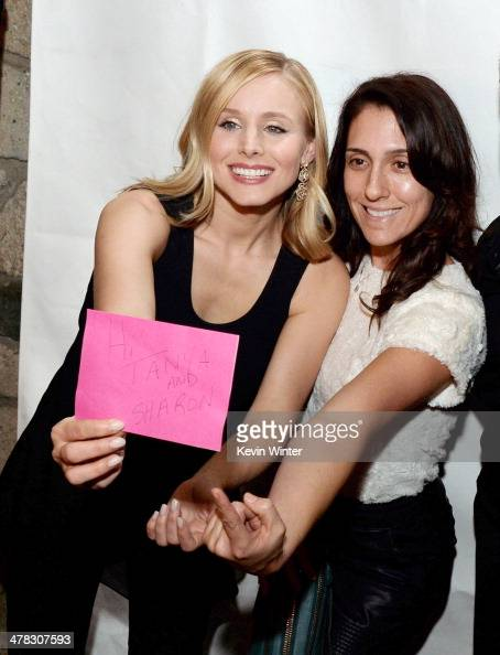 Actress Kristen Bell poses with a fan at the after party for the premiere of 'Veronica Mars' at Sadies Kitchen on March 12 2014 in Los Angeles...