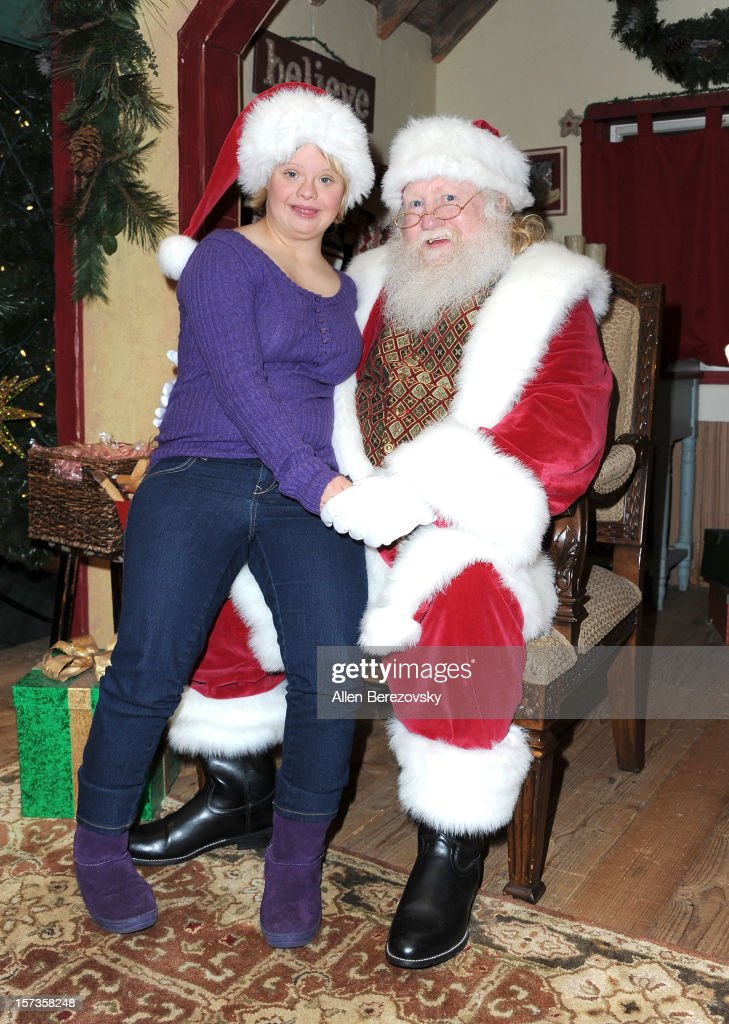 Actress Lauren Potter poses with Santa Claus at the Westminster Mall's Caring Santa event on December 2, 2012 in Westminster, California.