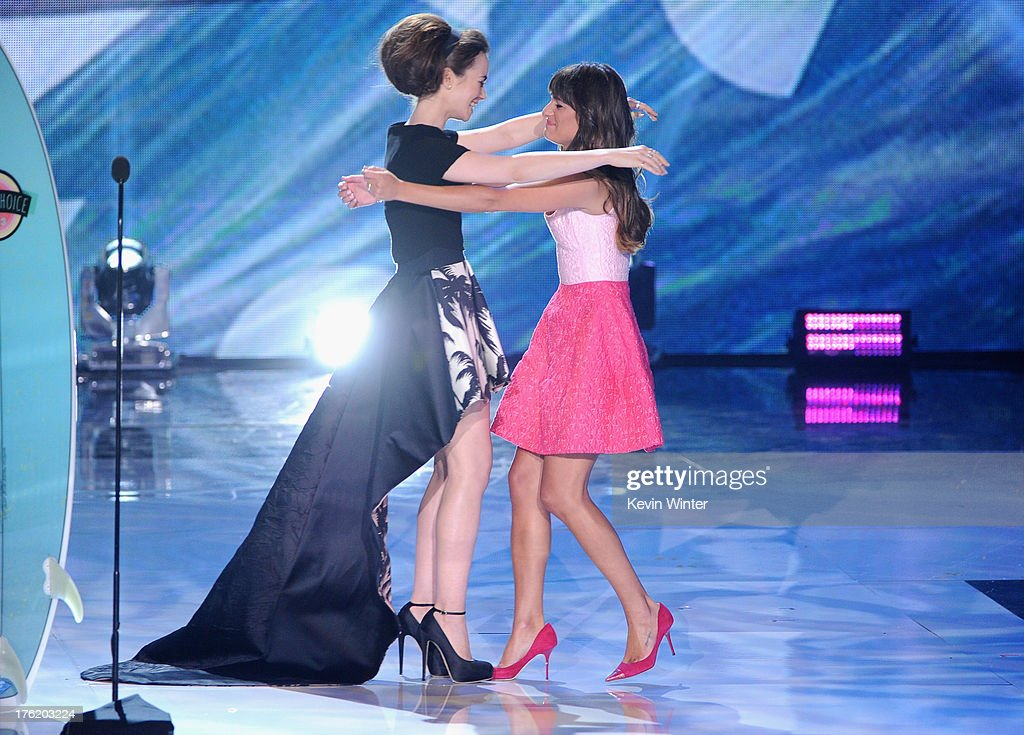 Actress Lea Michele (R) accepts Choice TV Show: Comedy award for 'Glee' from actress Lily Collins (L) onstage during the Teen Choice Awards 2013 at Gibson Amphitheatre on August 11, 2013 in Universal City, California.