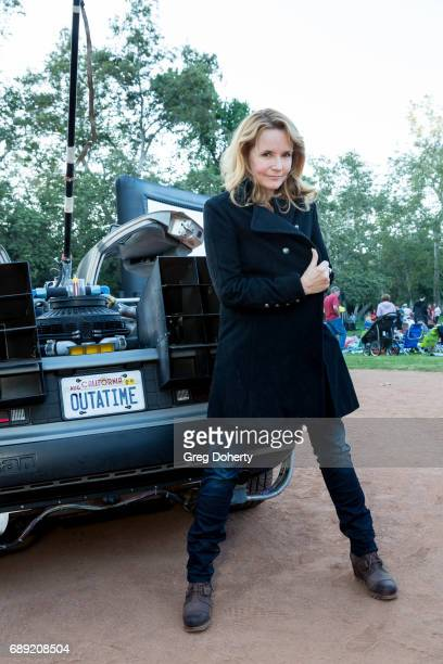 Actress Lea Thompson poses for a picture with a Delorean at the Street Food Cinema Welcomes 'Back To The Future' With Special Guest Lea Thompson at...