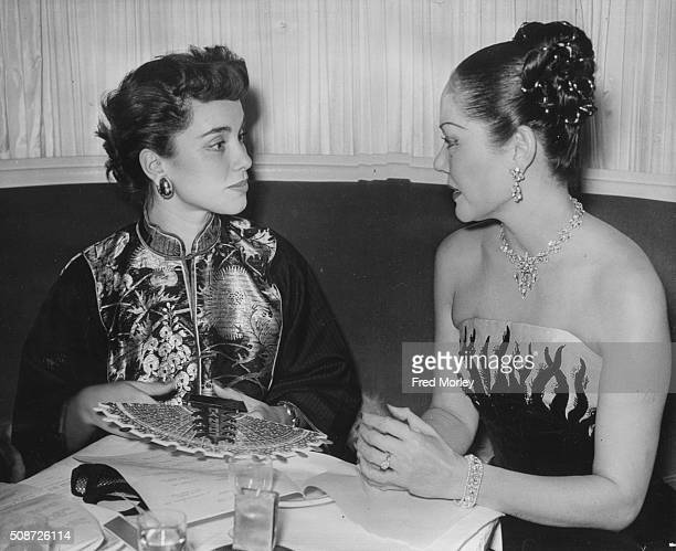 Actress Linda Christian wearing a traditional Chinese jacket and talking to Chineseborn compere Seignon at a Christmas Party held by Chen Yu nail...