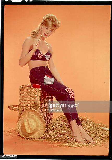 Actress Linda Evans is shown seated on a basket turned sideways wearing a jean top and jeans both with patches On the floor can be seen hay and a...