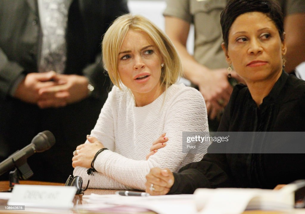 Actress <a gi-track='captionPersonalityLinkClicked' href=/galleries/search?phrase=Lindsay+Lohan&family=editorial&specificpeople=171623 ng-click='$event.stopPropagation()'>Lindsay Lohan</a> (L) and her attorney <a gi-track='captionPersonalityLinkClicked' href=/galleries/search?phrase=Shawn+Chapman+Holley&family=editorial&specificpeople=5763122 ng-click='$event.stopPropagation()'>Shawn Chapman Holley</a> during her arraignment for a felony count of grand theft on February 9, 2011 in Los Angeles, California. Lohan was charged with a felony count of grand theft for allegedly stealing a $2,500 necklace from a jewelry store in Venice.