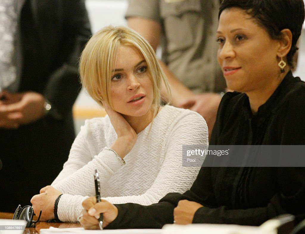 Actress <a gi-track='captionPersonalityLinkClicked' href=/galleries/search?phrase=Lindsay+Lohan&family=editorial&specificpeople=171623 ng-click='$event.stopPropagation()'>Lindsay Lohan</a> (L) speaks with her attorney <a gi-track='captionPersonalityLinkClicked' href=/galleries/search?phrase=Shawn+Chapman+Holley&family=editorial&specificpeople=5763122 ng-click='$event.stopPropagation()'>Shawn Chapman Holley</a> during her arraignment for a felony count of grand theft on February 9, 2011 in Los Angeles, California. Lohan was charged with a felony count of grand theft for allegedly stealing a $2,500 necklace from a jewelry store in Venice.