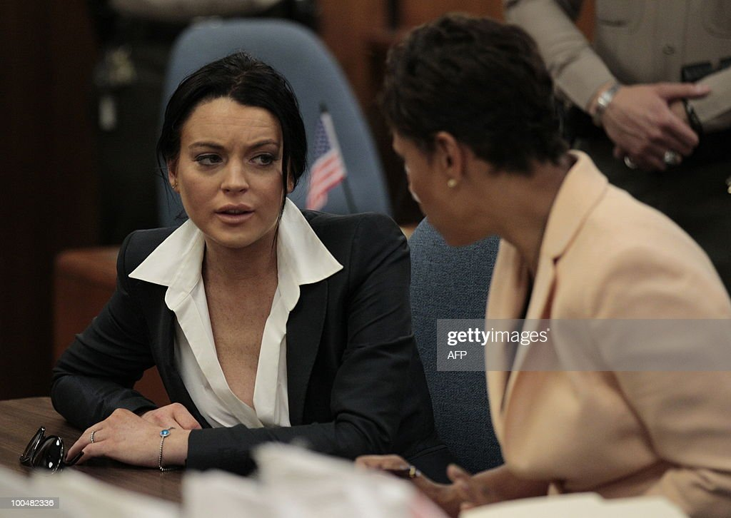 US actress Lindsay Lohan (L) speaks with her lawyer Shawn Chapman Holley during a hearing to respond to allegations she has not completed a set number of alcohol education classes, at the Beverly Hills Courthouse on May 24, 2010. Lohan who failed to appear for a court hearing in Los Angeles last week, prompted a judge to issue an arrest warrant that was later withdrawn when lawyers for the troubled actress posted bail. Lohan, 23, had been ordered to appear before Judge Marsha Revel to respond to allegations she has not completed a set number of alcohol education classes required under the terms of her probation. AFP PHOTO/POOL/Jae C. Hong