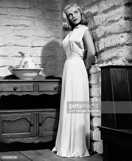 Actress Lizabeth Scott models the nightgown she wears as Paula Haller in the 1947 film Desert Fury The gown designed by Edith Head is made of light...