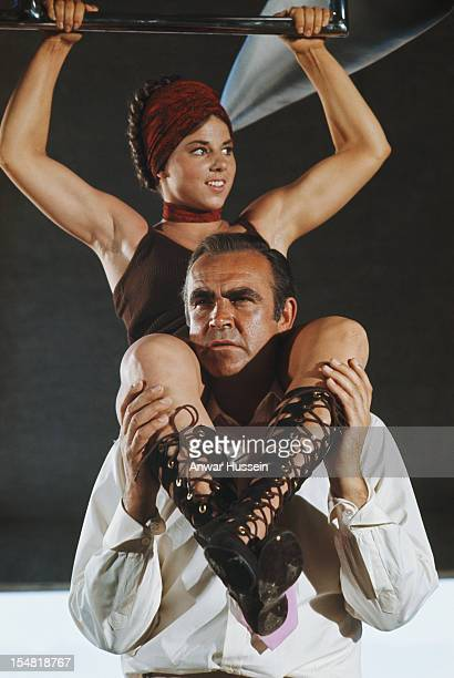 Actress Lola Larson as Bambi sitting astride the shoulders of Scottish actor Sean Connery on the set of the James Bond film 'Diamonds Are Forever'...
