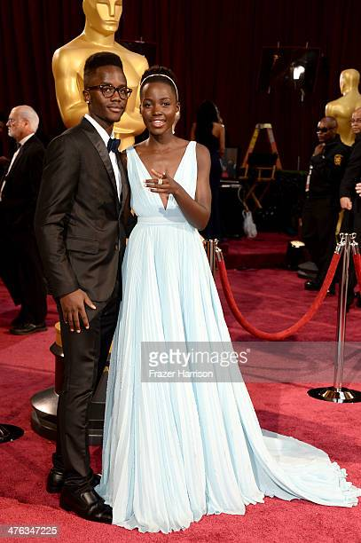 Actress Lupita Nyong'o and her brother Peter Nyong'o Jr attend the Oscars held at Hollywood Highland Center on March 2 2014 in Hollywood California