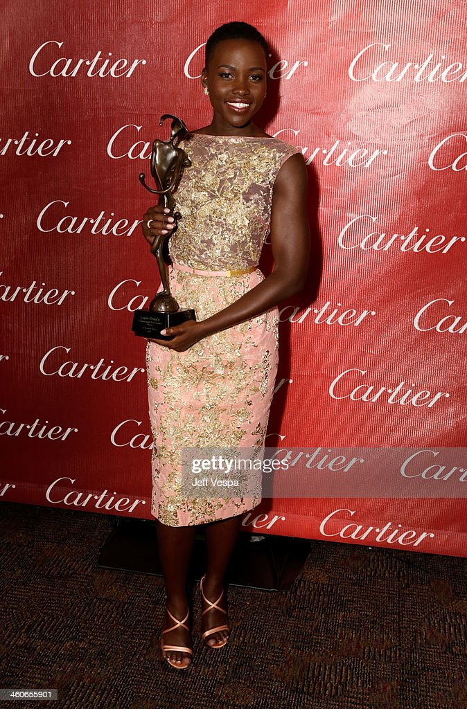 Actress Lupita Nyong'o poses with the Breakthrough Performance Award for '12 Years A Slave' backstage during the 25th annual Palm Springs...