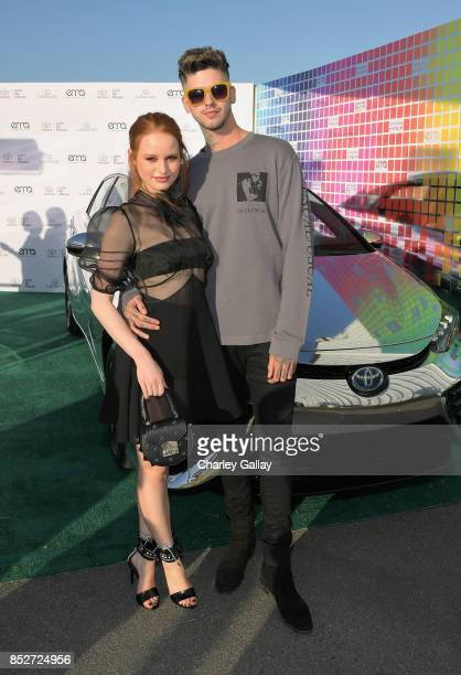 Actress Madelaine Petsch and rapper Travis Mills pose with the Toyora Mirai the zero emissions car during the 2017 EMA Awards Presented by Toyota on...