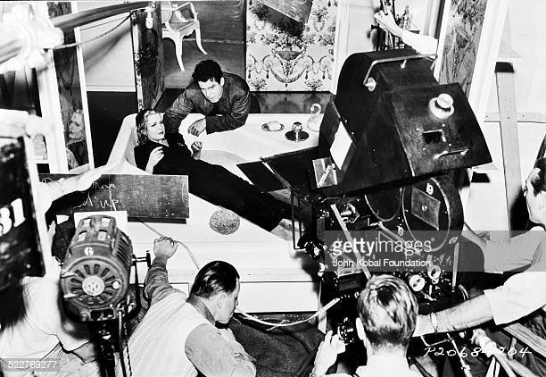 Actress Madeleine Carroll lying in a bathtub fully clothed and surrounded by camera crew on a movie set with Paramount Pictures 1939