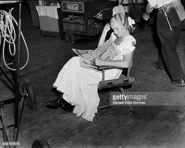 Actress Madeleine Carroll reads a news paper on set in Los Angeles California