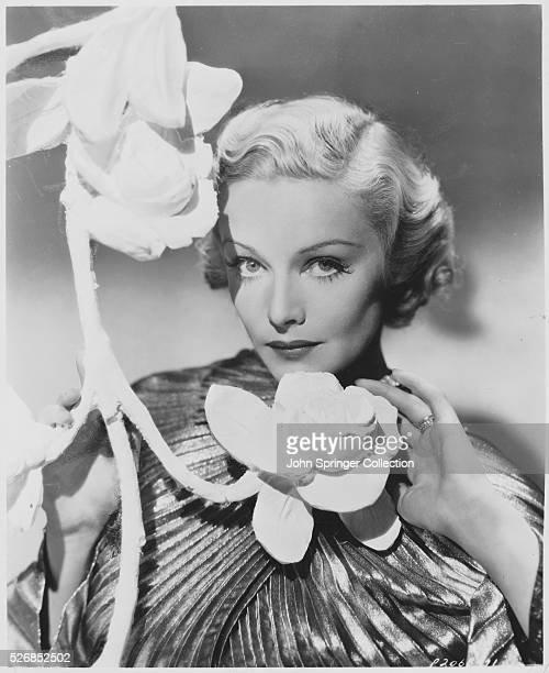 Actress Madeleine Carroll with a large artificial flower