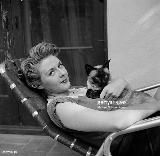 Actress Mala Powers poses with her cat at home in Los AngelesCA