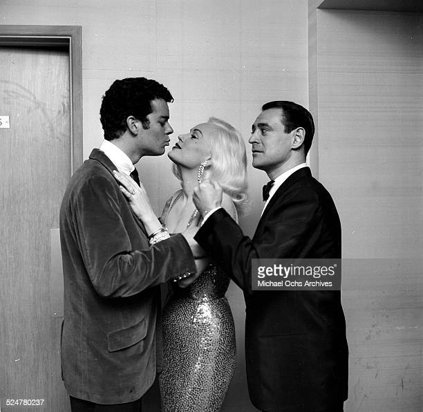 Actress Mamie Van Doren kisses a man as her husband Ray Anthony pretends to gets jealous during an event in Los AngelesCA