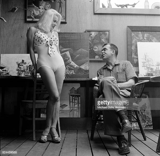 Actress Mamie Van Doren poses at home with photographers assistant in Los AngelesCA