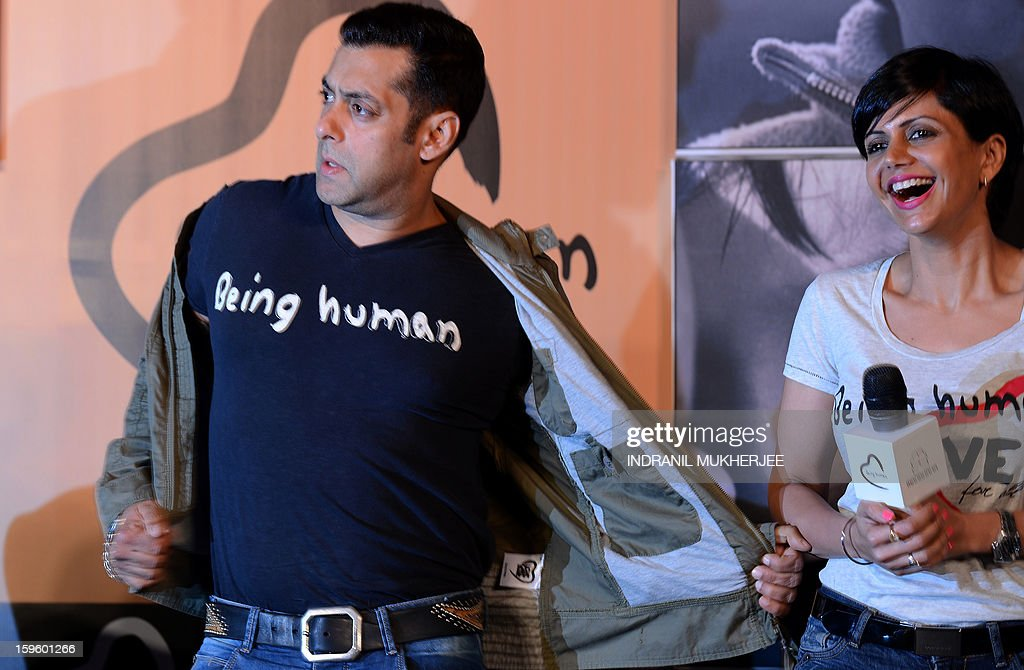 Actress Mandira Bedia (R) looks on as Bollywood film actor Salman Khan takes off his jacket during the launch of his 'Being Human' flagship clothing store in Mumbai on January 17, 2013. Khan announced the pan-India launch of his flagship retail store for 'Being Human' fashion apparel after having already launched in Paris, Belgium, Spain and Dubai.