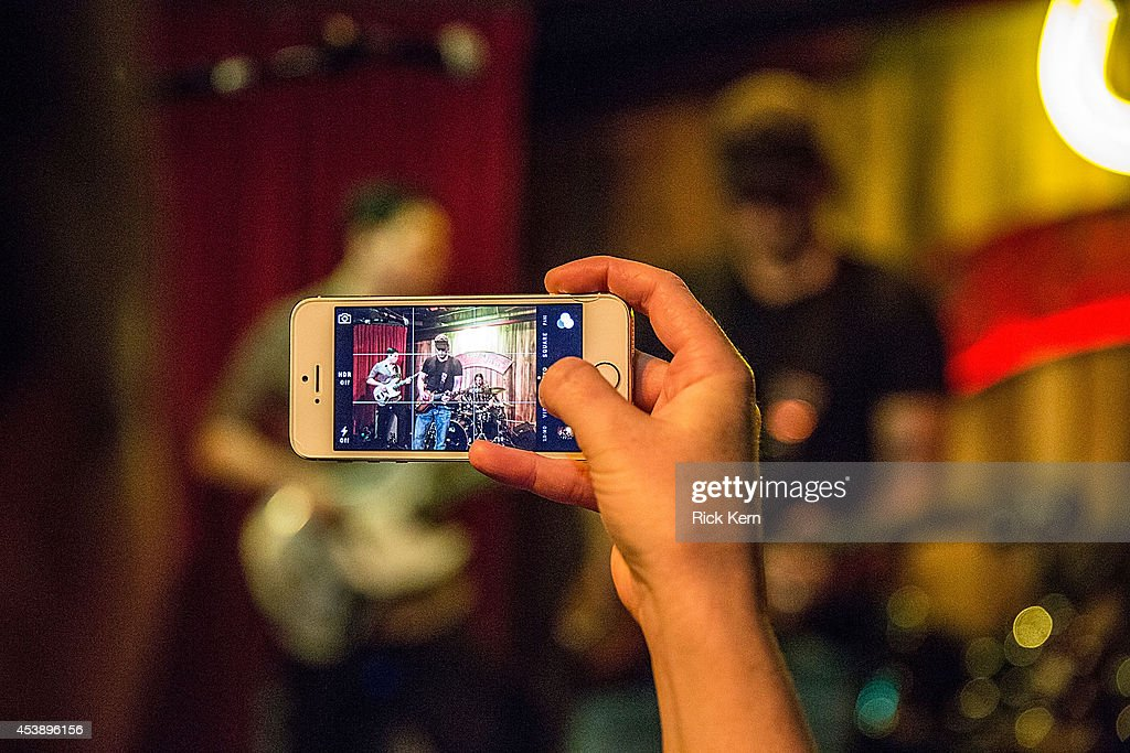 Actress Marci Madison takes a picture of her fiancé Robert Rodriguez performing on stage with his band Chingon during the 'Sin City: A Dame to Kill For' premiere after party at The Rattle Inn on August 20, 2014 in Austin, Texas.