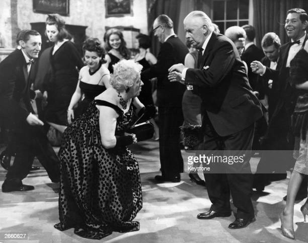 Actress Margaret Rutherford doing the twist with her husband in a scene from the Agatha Christie film 'Murder at the Gallop' The film was directed by...