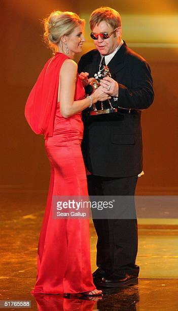Actress Maria Furtwangler presents musician Elton John with his Bambi Award for Charity at the Bambi Awards 2004 at the Theater im Hafen on November...