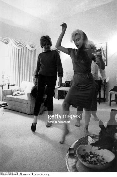 Actress Marilyn Monroe dances with martini in hand during party at producer Henry Weinstein's home January 20 1962 in Hollywood California