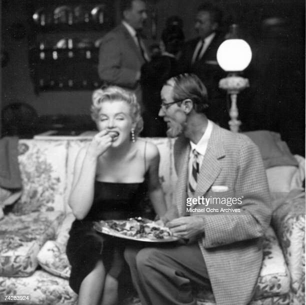 Actress Marilyn Monroe eats and chats with photographer Earl Leaf at a party held in her honor wearing a black dress and white gloves at the Beverly...