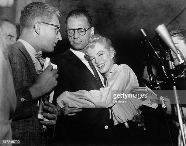 Actress Marilyn Monroe hugs playwright Arthur Miller as an unidentified reporter looks on during their sidewalk interview in front of her apartment...