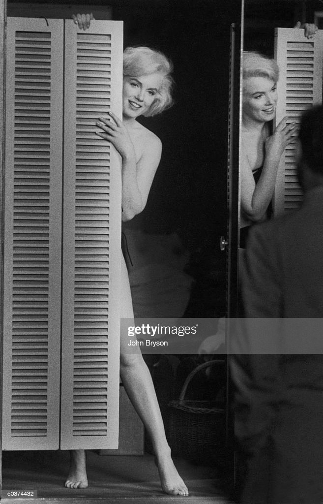 Actress <a gi-track='captionPersonalityLinkClicked' href=/galleries/search?phrase=Marilyn+Monroe&family=editorial&specificpeople=70021 ng-click='$event.stopPropagation()'>Marilyn Monroe</a> peering out at her husband Arthur Miller fr. behind door after putting on sexy bikini bathing suit she purchased, w. the price tag still on it, to see if he approves, at studio after work on movie Let's Make Love.