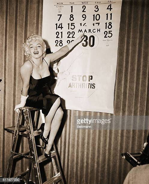Actress Marilyn Monroe points to the encircled date March 30th the day she'll ride an elephant a pink one for the sake of charity on the New York...
