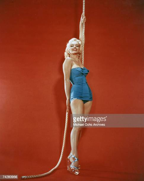 Actress Marilyn Monroe poses for a portrait holding on to a rope wearing a blue bathing suit and glass high heels in circa 1952