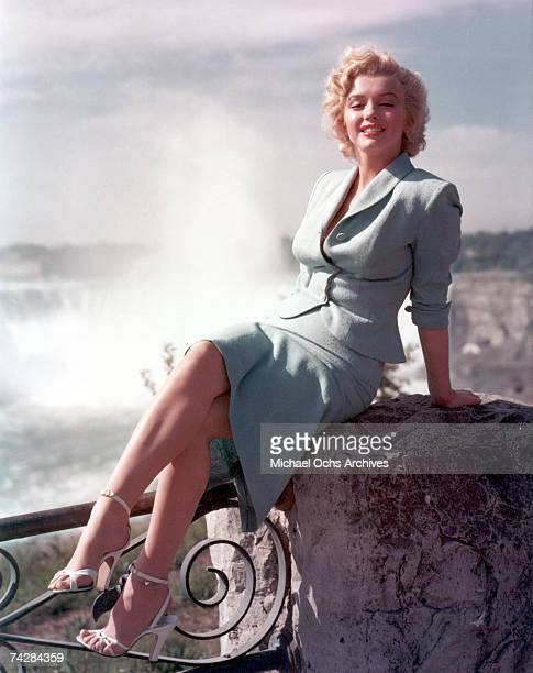 Actress Marilyn Monroe poses for a portrait in front of Niagara Falls dressed as Rose Loomis from the film 'Niagara' which was released on January 21...