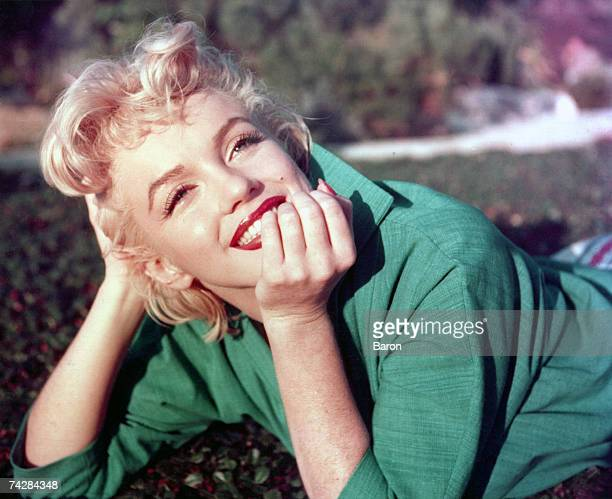 Actress Marilyn Monroe poses for a portrait laying on the grass in 1954 in Palm Springs California