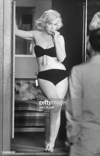 Actress Marilyn Monroe posing for husband Arthur Miller fr in dressing rm doorway after putting on sexy bikini bathing suit she purchased w the price...
