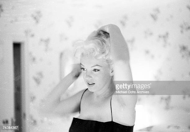 Actress Marilyn Monroe prepares to go out to the play 'Cat On A Hot Tin Roof' by applying makeup and perfume in her hotel room at the Ambassador...
