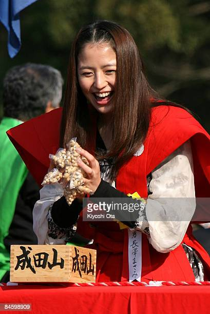 Actress Masami Nagasawa throws packs of beans to visitors during a beanscattering ceremony at Shinshoji Temple on February 3 2009 in Narita Chiba...