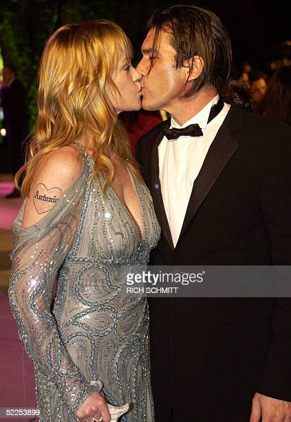 Actress Melanie Griffith and actor husband Antonio Banderas share a kiss at the Vanity Fair Dinner and Post Party celebrating the 77th Academy Awards...