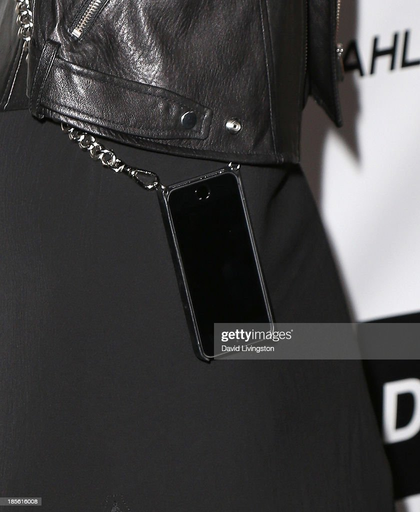 Actress Mena Suvari (iPhone and chain detail) attends the Dahlia Wolf Launch Party at the Graffiti Cafe on October 22, 2013 in Los Angeles, California.