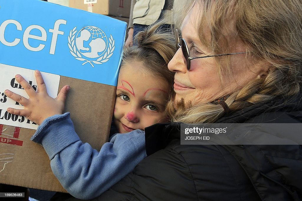 US Actress Mia Farrow (R), a UNICEF goodwill ambassador, distributes clothes to Syrian refugees in Baalbek, in the Lebanese Bekaa valley on January 15, 2013. Farrow is on a two day visit to Lebanon, meeting Syrian refugees. AFP PHOTO/JOSEPH EID