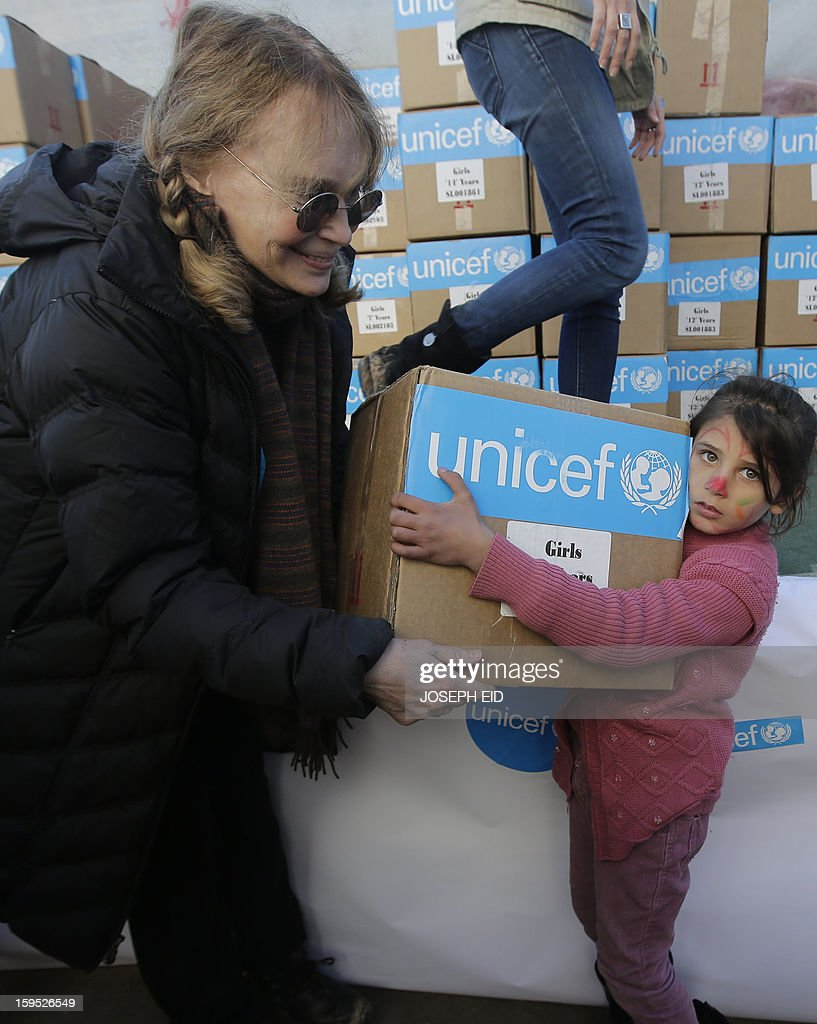 US Actress Mia Farrow (L), a UNICEF goodwill ambassador, distributes clothes to Syrian refugees in Baalbek, in the Lebanese Bekaa valley on January 15, 2013. Farrow is on a two day visit to Lebanon, meeting Syrian refugees. AFP PHOTO/JOSEPH EID