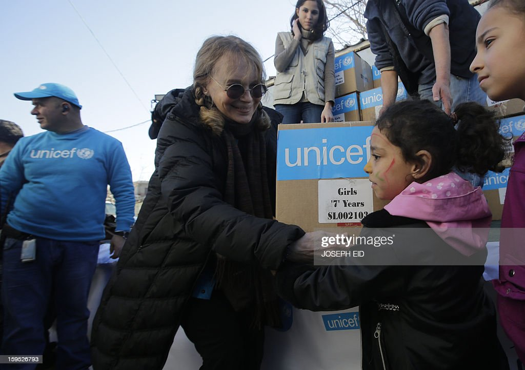 US Actress Mia Farrow (C), a UNICEF goodwill ambassador, distributes clothes to Syrian refugees in Baalbek, in the Lebanese Bekaa valley on January 15, 2013. Farrow is on a two day visit to Lebanon, meeting Syrian refugees.