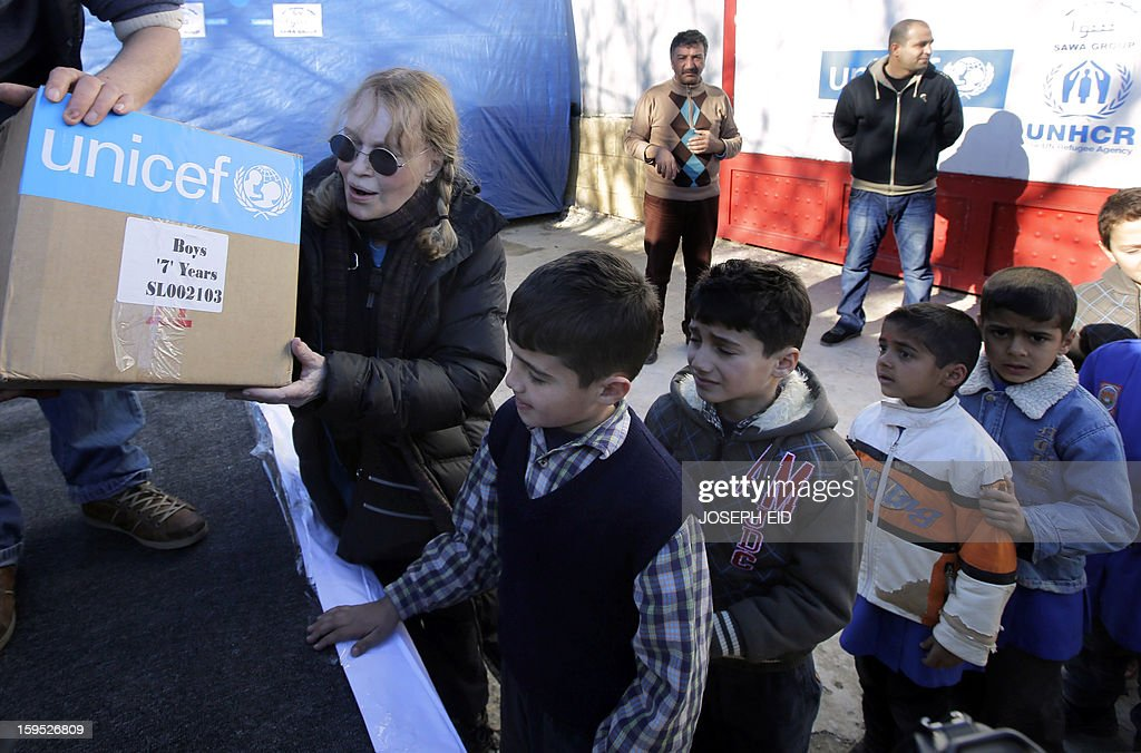 US Actress Mia Farrow (L), a UNICEF goodwill ambassador, distributes clothes to Syrian refugees in Baalbek, in the Lebanese Bekaa valley on January 15, 2013. Farrow is on a two day visit to Lebanon, meeting Syrian refugees.