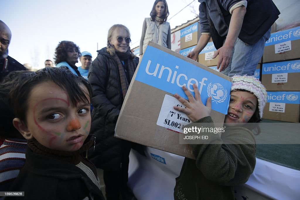 US Actress Mia Farrow (C), a UNICEF goodwill ambassador, distributes clothes to Syrian refugees in Baalbek, in the Lebanese Bekaa valley on January 15, 2013. Farrow is on a two day visit to Lebanon, meeting Syrian refugees. AFP PHOTO/JOSEPH EID