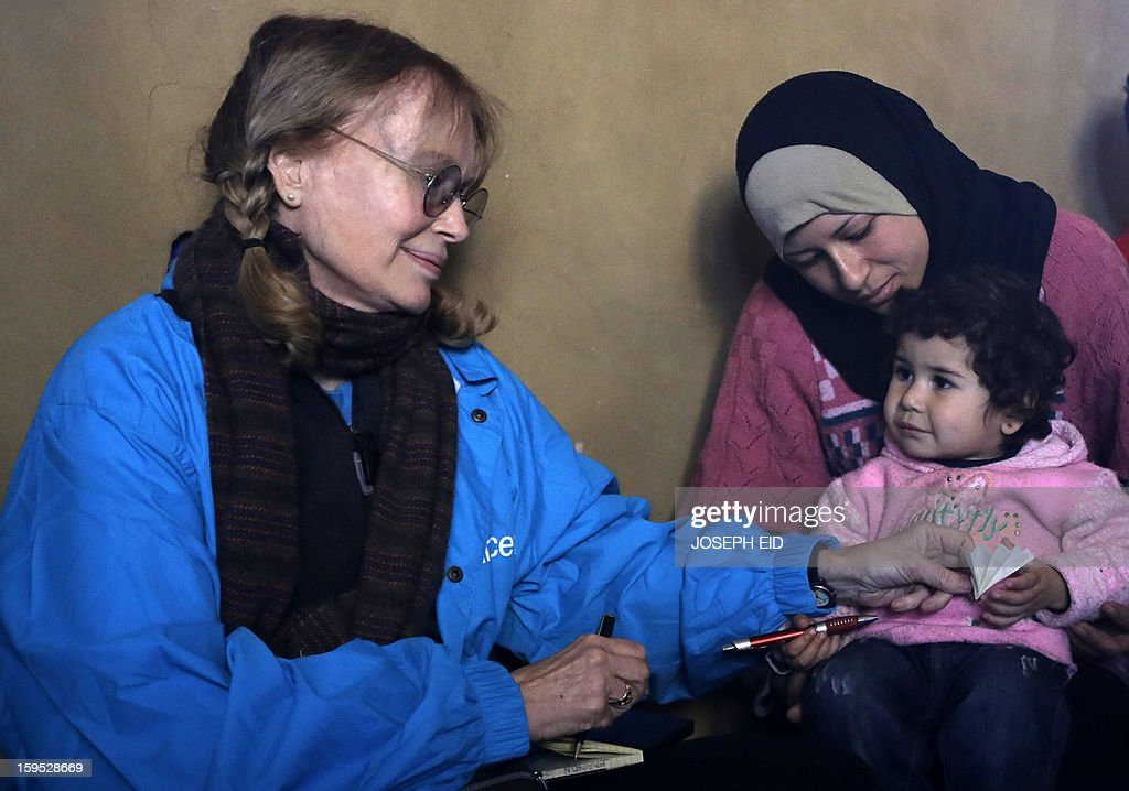 US Actress Mia Farrow, a UNICEF goodwill ambassador, looks at a child as she visits Syrian refugees in Baalbek, in the Lebanese Bekaa valley on January 15, 2013. Farrow is on a two day visit to Lebanon, meeting Syrian refugees.