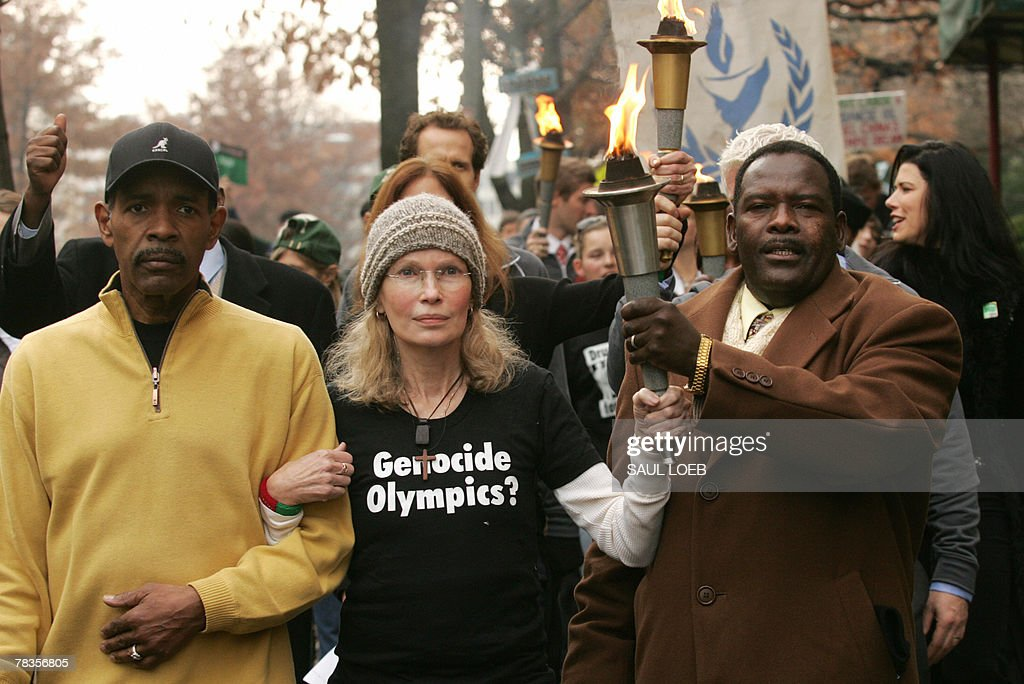 US Actress Mia Farrow (C) carries an Olympic-style torch as she walks with radio host Joe Madison (L) and Mohamed Yahya (R) of Darfur, Sudan, to China's embassy as part of a march sponsored by the Save Darfur Coalition to mark International Human Rights Day with a Dream for Darfur Torch Relay through the streets of Washington, DC, 10 December 2007. The march strives to 'remind China of its responsibilities' in the Darfur region as it prepares to host the 2008 Olympics. AFP PHOTO/SAUL LOEB