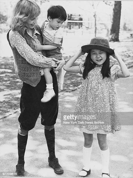 Actress Mia Farrow holds son Misha in her arms as daughter Soon Yi Previn tries on mom's hat in Central Park